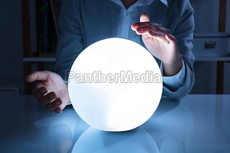 businesswoman hand on crystal ball