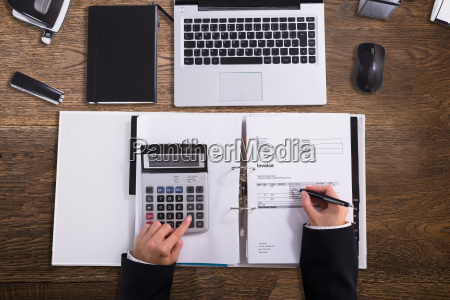 businessperson calculating bill with calculator