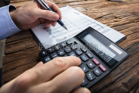 businessmans hand calculating financial data with