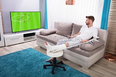 man with broken leg watching football