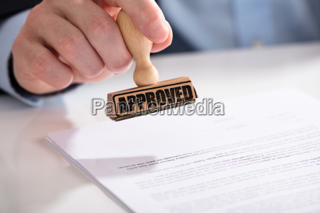 businessperson using stamper on document with