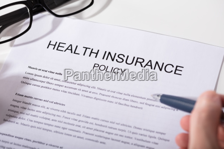 person holding pen over health insurance