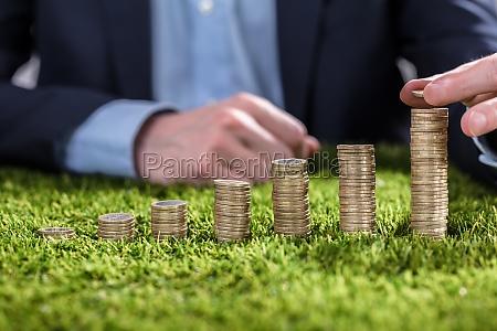 wirtschaftler der muenzen auf gras stapelt