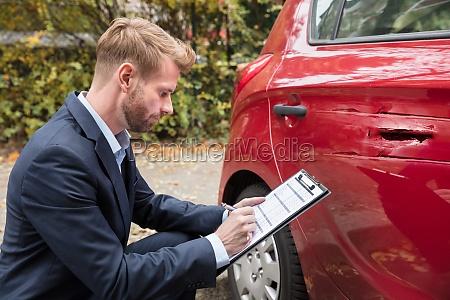 versicherungsagent der auto nach unfall ueberprueft