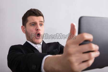 happy businessman looking at digital tablet