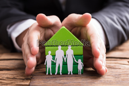 businessperson protecting house model and family