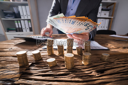 businessperson calculating euro banknotes