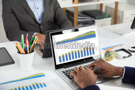 two businesspeople analyzing financial graph on