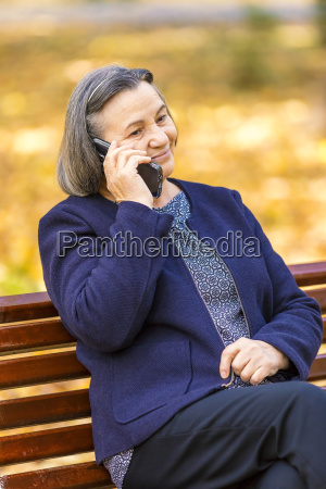 senior woman talking on smartphone outdoors