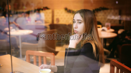 woman behind window in cafe young