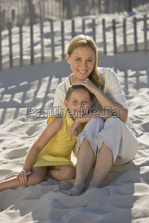 mother and daughter sitting on beach