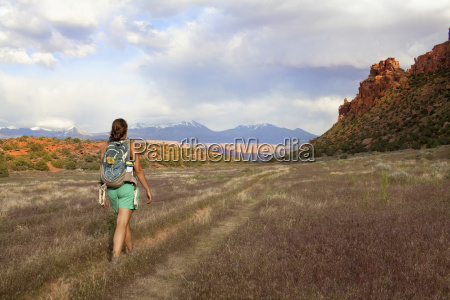 woman with backpack walking in grass