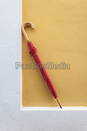 red umbrella propped up against wall