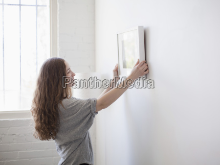 young woman hanging picture on freshly