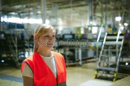 portraet einer mitarbeiterin in orangefarbener robeweste