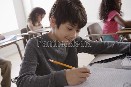 portrait of schoolboy 12 13 writing