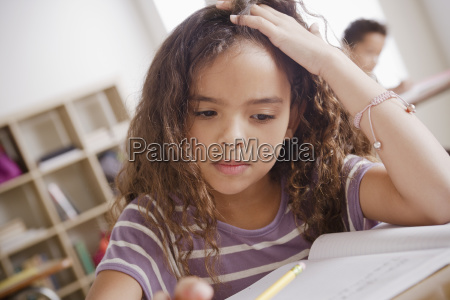 schoolgirl focused on writing in classroom