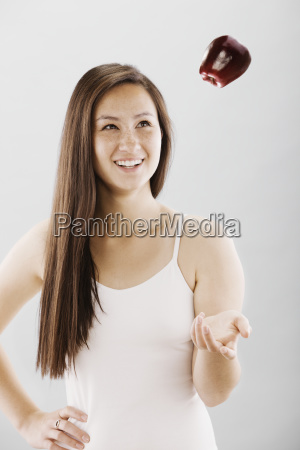 woman tossing a red apple