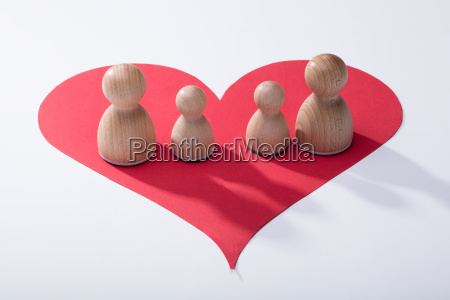 wooden pawns on red heart shape