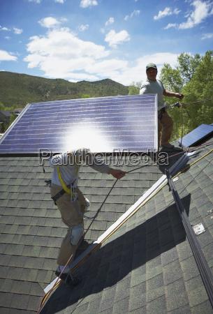 bauarbeiter die sonnenkollektoren auf dach installieren