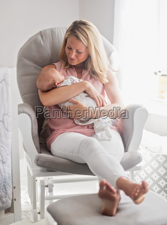 mother sitting in armchair and holding