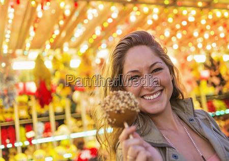 woman holding caramel apple at funfair