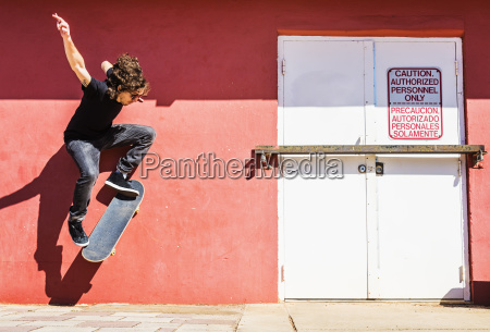 man skating near red wall