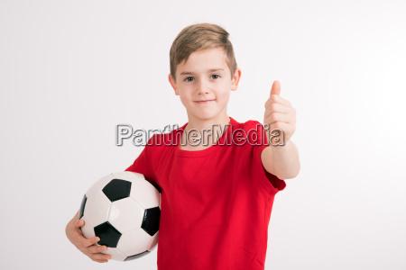 junge im roten hemd mit fussball