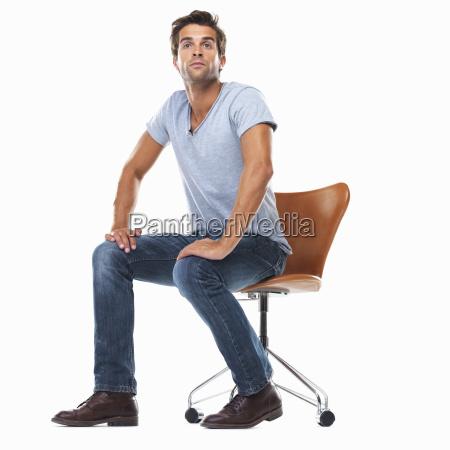 studio shot of young man sitting