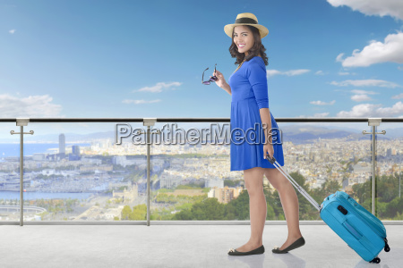 pretty asian woman pulling suitcase