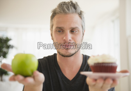 man weighing green apple against cup