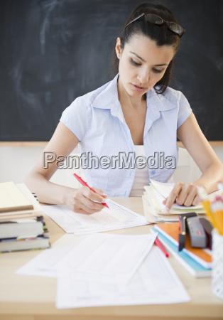 lehrerin schreibt am schreibtisch
