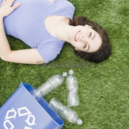 frau liegt auf gras neben recycling