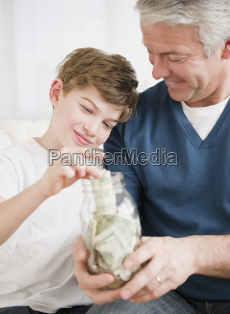 father and son putting money in