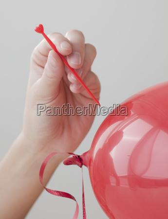 frau die roten ballon knallt