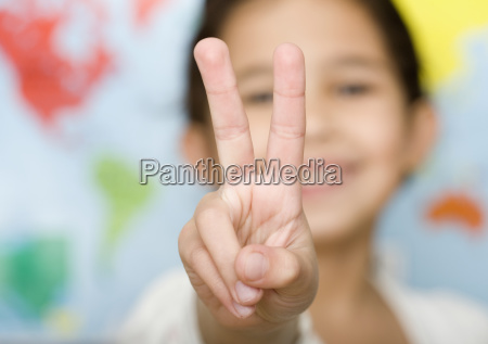 child making peace sign hand gesture