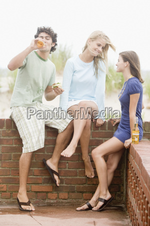 friends leaning on brick wall