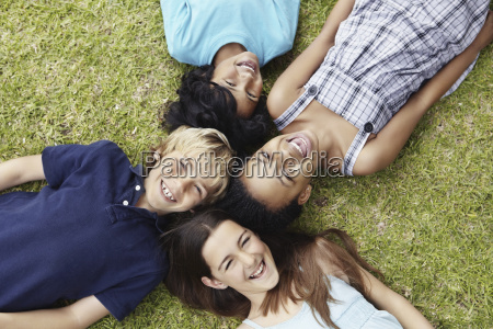 four friends lying on the grass