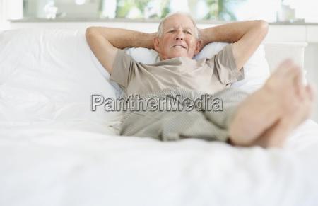 entspannter aelterer mann der auf bett
