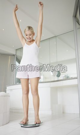 happy woman standing on bathroom scale