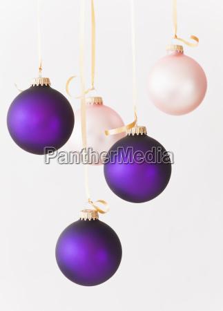 atelieraufnahme von purpurroten und rosa weihnachtsverzierungen
