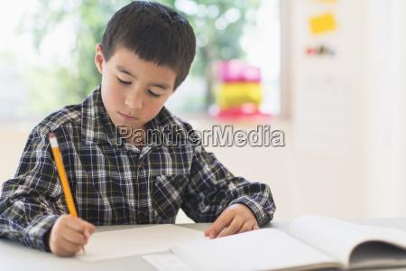 boy 6 7 writing at school