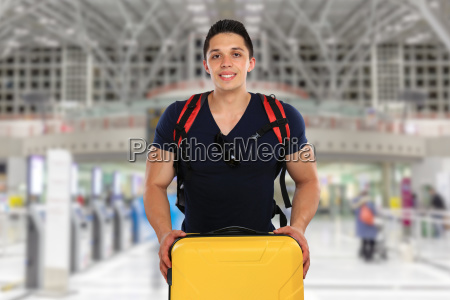 young man traveling with suitcase airport