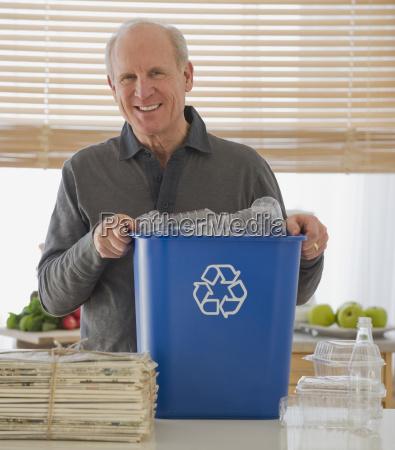 senior man holding recycling bin