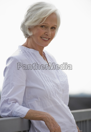 senior woman leaning on railing