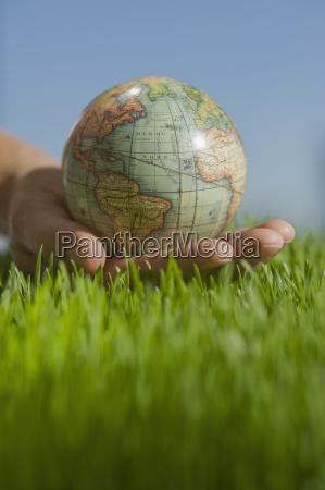 close up of hand holding globe