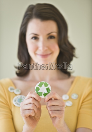 woman holding button with recycling symbol