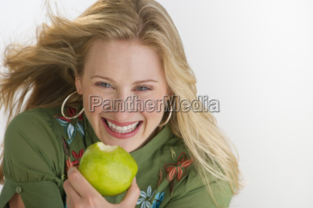 happy blond woman eating an apple