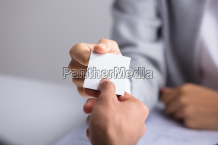 businessperson giving card to partner