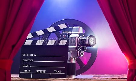 filmkamera mit clapperboard und filmrolle auf